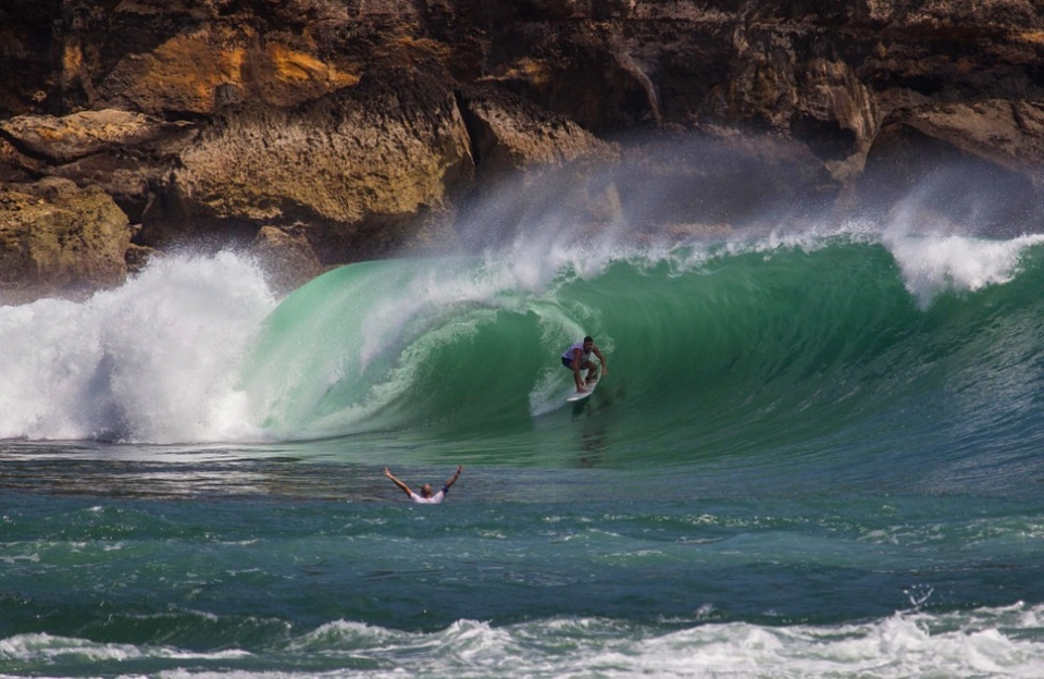 Peer pressure? A pair of surfers charge slabs somewhere along Java's rugged coastline.