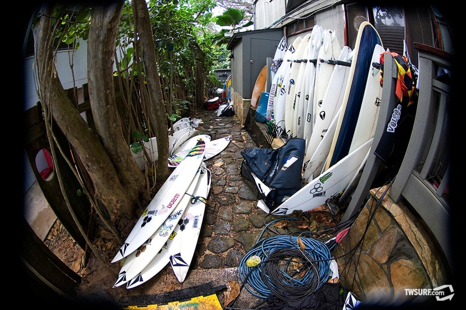 Boards, boardbags, trunks, and enough cables to ring the island of Oahu litter the side yard of the Volcom house.