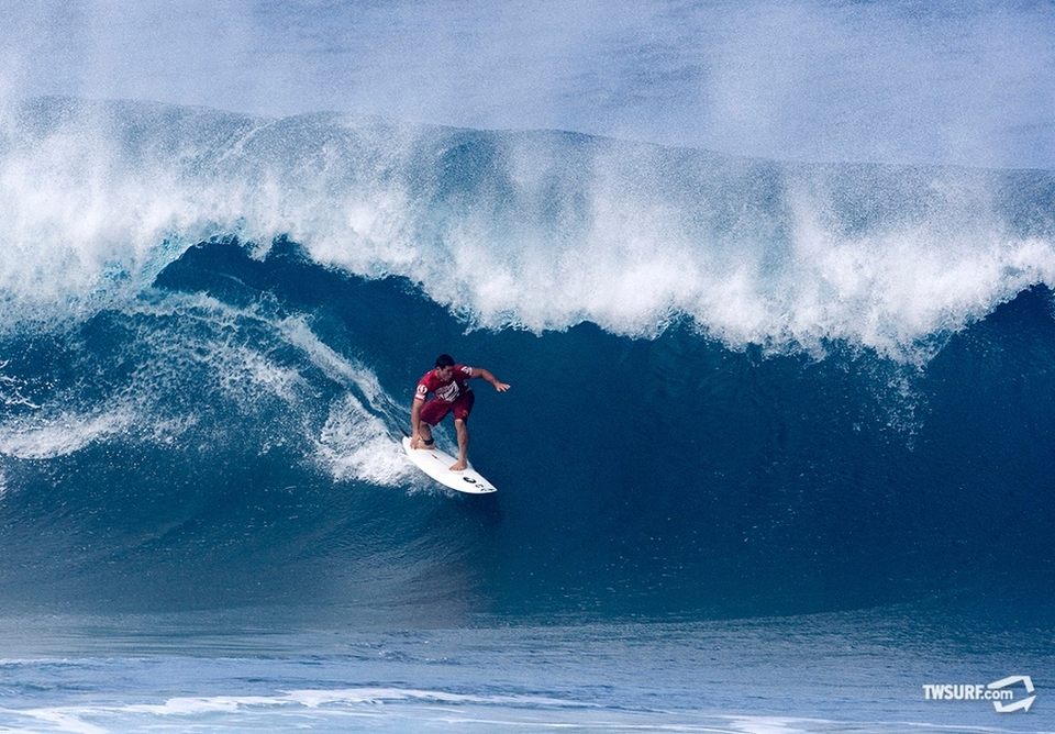 Sporting his red lifeguard trunks, Dave Wassel charges into the abyss at Pipeline