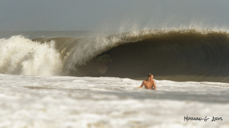 You have to look twice... Sebastian Moreno buried deep in a Hurricane Sandy pit off Melbourne Beach in Florida.