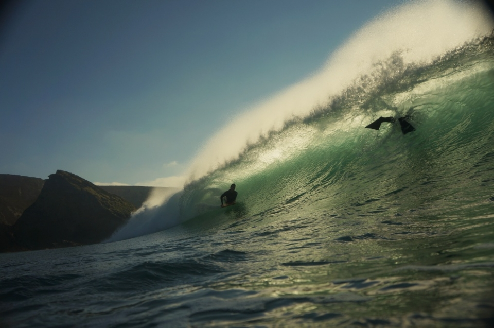 One of the healthy contingent of Porthtowan bodyboarders slides under a feathering backlit lip.