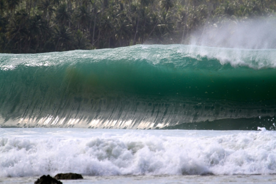 Lagundri Bay, Indonesia.  On this day all the locals said it was bigger than the J.O.B swell. All the kids were screaming tsunami when the big set started coming and waves were hitting the bottom of the bungalows .  It was very heavy wave, when the lip hit the reef it was like a big explosion. The night before I can't really sleep! Too noisy as the bungalow was less than 100 meters from the wave.  This swell was 11ft 19sec SSW. Only 3 surfers paddled out between 1pm to 3pm; local legend, Anthon, and two pro surfers, Mikala Jones and Dean Morisson!  Afterward, more surfers started coming but no one caught the bombs. It would have been better to tow in!  I have been travelling for 10 years in Indonesia and have never seen such a powerful wave like this day.