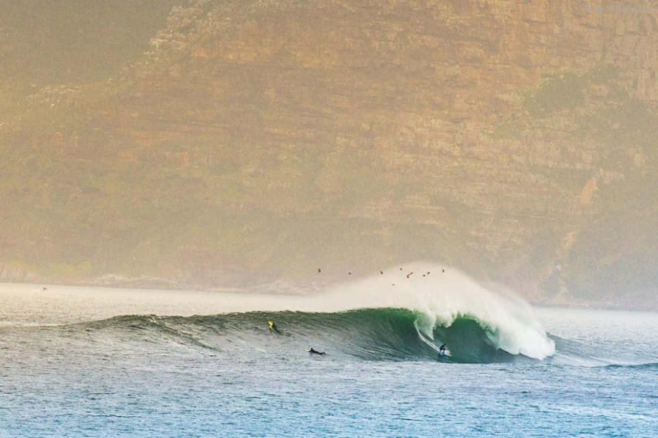 """Sunset, South Africa.  The swell wasn't necessarily a big on for spots like Dungeons and Sunset, but with the period at 20 seconds and all the other elements seemingly connecting, we all woke early to check out what the spots were doing.  Sunset is a good gauge to know what some of the other spots are doing, so I checked that first.  At first light only 2 or 3 locals were on it.  Sunset can be a heaving death pit on a heavy day.  This day, however, was clean and glassy with 15 – 20 ft clean glassy barrels.  It was the perfect day for younger and new big wave surfers to test their mustard and pop their big wave cherry – and for the hardened regulars, it was a fun day to be more daring and to try to get stuck in to triple overhead barrels.  The sets were very far apart, up to a 30 minute wait, but when they came there were 10 waves or more in each set.  The boys were catching one of the first few waves in the set and able to paddle back and catch one of the last.  A rare clean, glassy day – definitely a highlight day of the season, and no skis."""""""