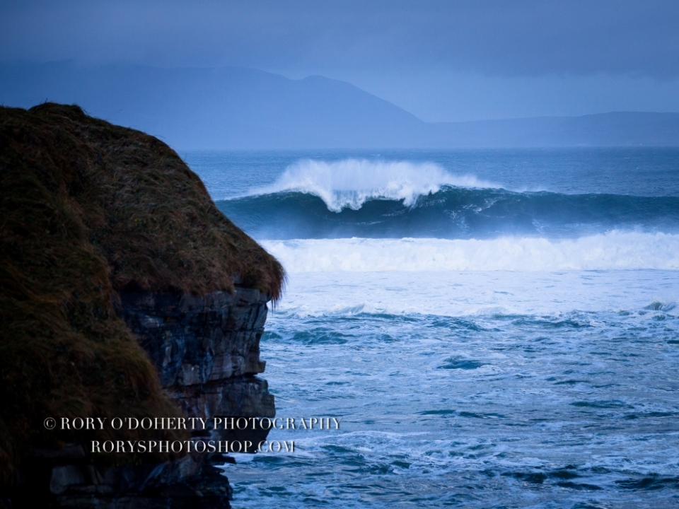 Mullaghmore, Ireland.  That picture in particular is a favourite as it captures well the power of Mother Nature, the rough & rugged atmosphere of Irish surf, and shows just how big our waves do get. It was a typical Irish winters day that, with huge waves crashing in, early in the mystical morning. Following some extreme rain and winds, a few perfectly angelic rays of sunshine managed to pierce their way through in the morning the late afternoon. With the crowd gathered and the brave surfers, I guess one couldn't help but feel a part of something really real and raw. It was exhilarating, intense and definitely insane! I think everyone left that day feeling truly alive.