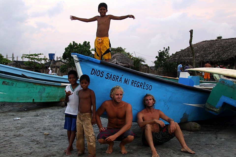 "Enjoying the sunset with local kids in northern Ecuador.  We tandem surfed with them for several days and taught them the basics of surfing.  The name of the boat means ""God will know my return"", symbolizing our timeless adventure that started on July 8th 2010"
