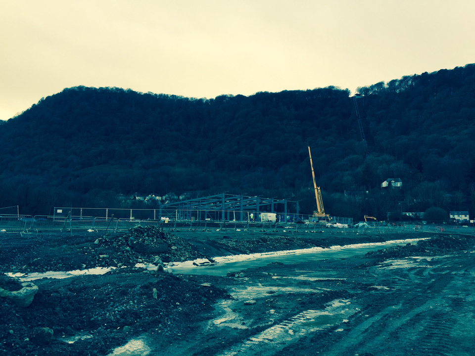 Steel frames rising above the concrete pan at Surf Snowdonia