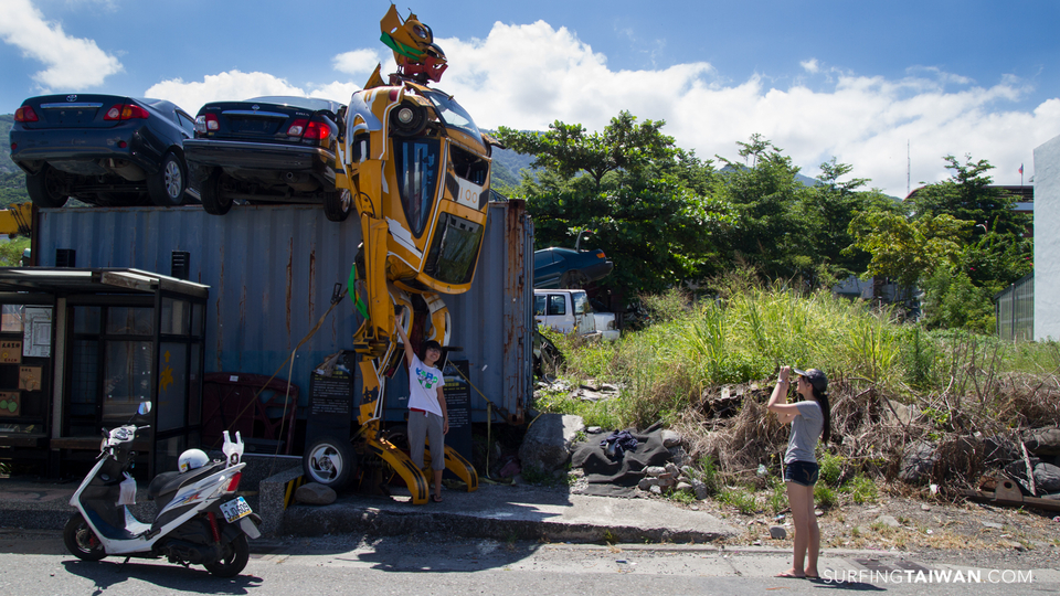 Two Taiwanese girls enjoy the chance to take pictures with a Transformer. How this came to rest in a sleepy fishing/farming village on the coast of Taiwan still makes me smile.