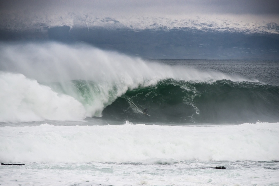 Sebastian Steudtner charging massive Mullaghmore, while the mountains in the background are covered in fresh snow.