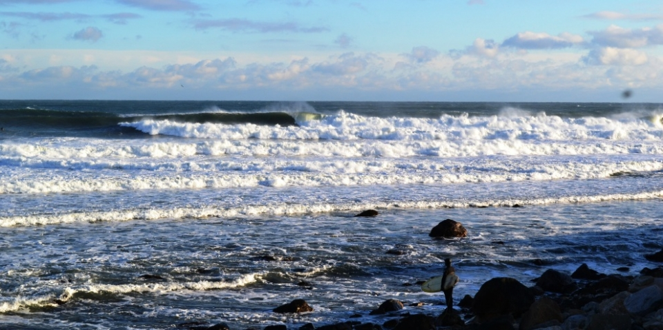 A lone wave slider mentally prepares for the paddle in Rhode Island.