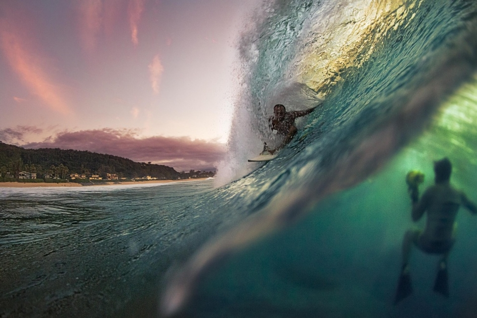 Pipeline, Oahu.   I managed to snap this freakish shot during a beautiful Hawaiian sunset. My friend Matt Catalano was filming underwater and by chance the water shifted over my lens at the perfect moment to capture him in action. With the barrel, the mountains and the underwater scene I can't imagine another image so perfectly capturing the North Shore experience.