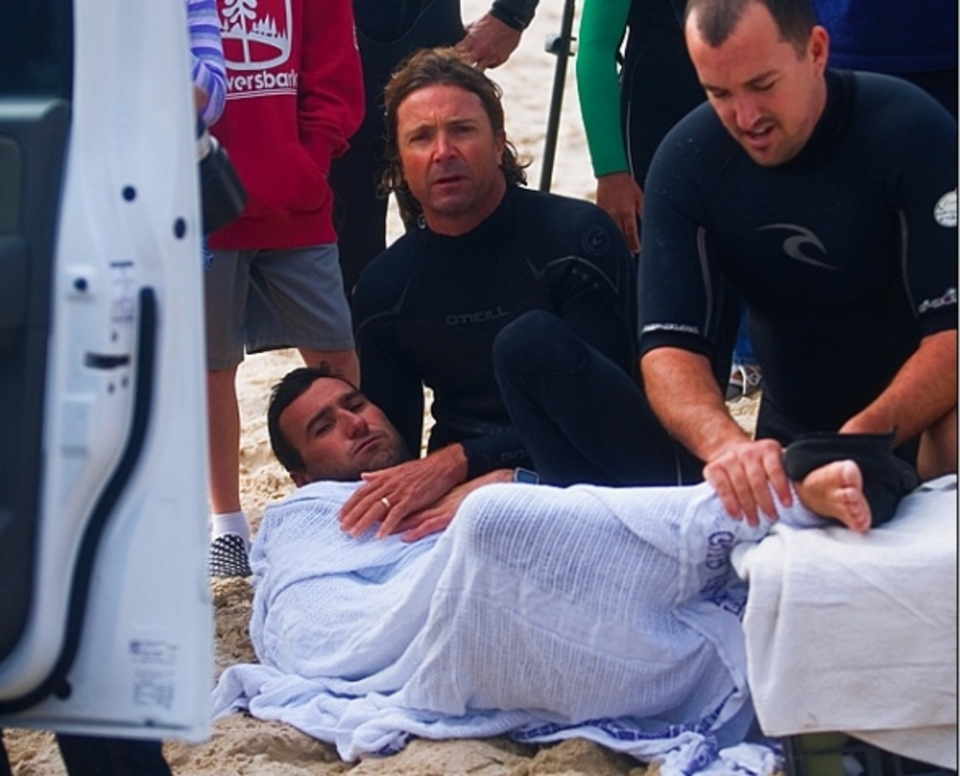 Fellow surfers stem the blood flow on shore, moments after foot met fin.
