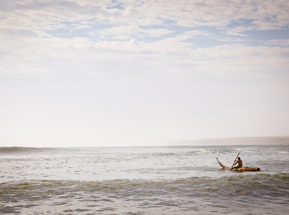 A local fisherman in Punta Huanchaco paddles out on his caballito de totora. These wave riding reed boats have been used in Peru for over three thousand years for fishing. Being able to ride waves back to shore was a necessity for the early fisherman due to size and consistency of waves on the coast here. Some historians argue these are were the world's first surf craft.   In 2012, Save the Waves Coalition approved Punta Huanchaco as a World Surfing Reserve due to its ancient wave riding culture.