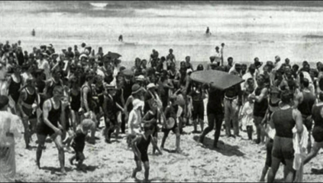 Duke carrying his board up the beach at Freshwater in 1914.